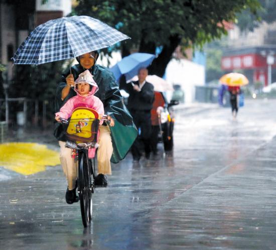 康王路上,家长骑车举伞送孩子上学