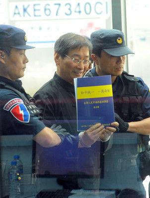 """张安乐返台时手持""""和平统一、一国两制""""的宣传手册。"""