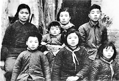 """焦裕禄在世时,这个大家庭没有一张""""全家福""""。他去世两年后,徐俊雅和6个子女在家门前合影(资料照片)"""