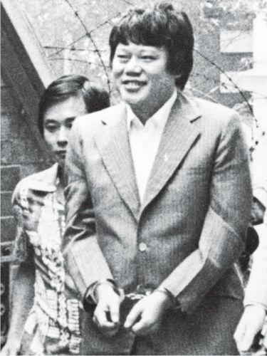 戴上手铐的马惜珍当年被押时面露笑容,任由在场记者拍摄。图片来源《明报》