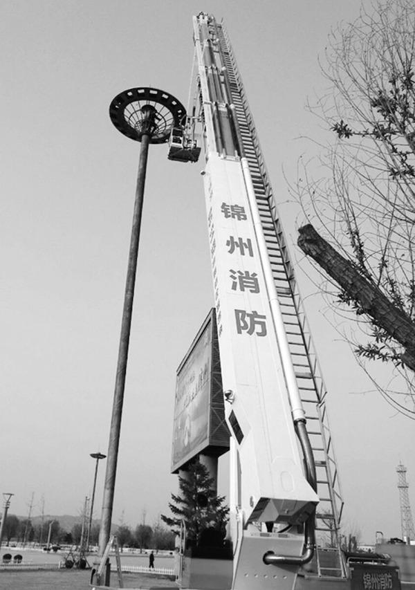 高清图—锦州南站广场电工李春田随高杆灯伞5秒直冲30米高空