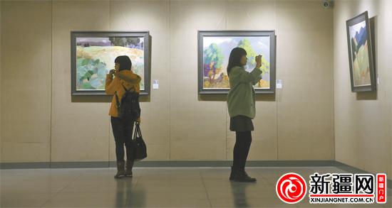 """11月12日,在乌鲁木齐市美术馆,观众正在参观""""激活正能量""""中国当代油画家学术推介展。(记者蒋晓摄)"""