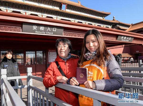 12月3日,一名教师(右)在故宫博物院入口处展示教师资格证。