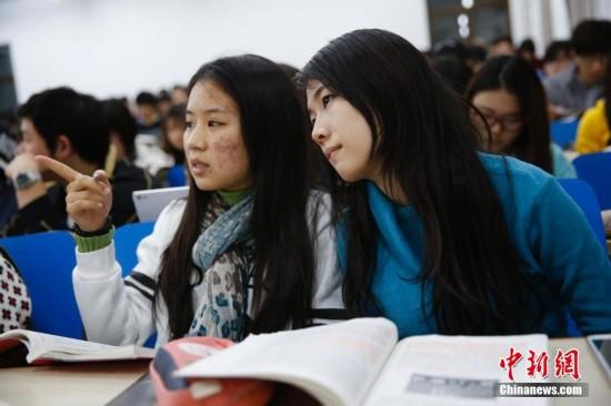 来自泰国的华裔留学生李慧敏、白云莹考入北京大学国际关系学院已有三个月的时间。近日,中国国务院总理李克强复信李慧敏和白云莹,以学长的身份对她们表达了祝愿和期许。受到鼓励的两名李慧敏和白云莹希望能够尽早克服学业上的困难,适应在中国的生活。图为12月14日,泰国华裔留学生李慧敏(左)和白云莹(右)在北京大学校门前身着北京大学国际关系学院校服合影。中新社发 王骏 摄