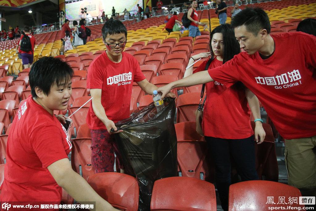 国足球迷赛场捡垃圾 球迷和球员同样赢得世界