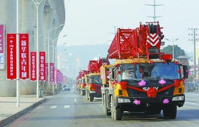 昨天上午,六辆巨型吊车组成的迎亲车队行驶在五里界至花山的路上。