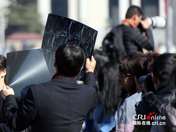 2015年3月13日,全国政协十二届三次会议在北京闭幕。会前,全国政协委员、北京大学国际医院院长陈仲强在大会堂外接过工作人员递上的医疗影像,现场为患者诊疗。图片来源:cfp
