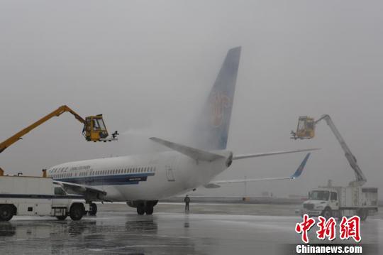 机务人员利用加温机烤除飞机机翼下表面,起落架及发动机区域的冰霜.