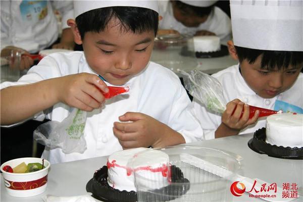 小朋友们动手制作六一生日蛋糕 人民网武汉6月1日电 5月31日,以红领巾相约中国梦梦从这里起航为主题,武汉市庆祝六一国际儿童节游乐活动在市青少年宫举行,给孩子们送上了一份丰厚的六一国际儿童节贺礼。 当日上午九时,庆祝六一国际儿童节文艺演出在市青少年宫音乐厅精彩上演,架子鼓独奏《花样年华》拉开了游乐活动的帷幕。小朋友们表演的歌舞、器乐演奏、单口相声、京剧清唱等节目,受到近800名小朋友的热捧,现场气氛欢快活泼、笑声不断。来自武汉市青少年宫爱心课堂的两名自闭症学员倾情演奏的钢琴齐奏