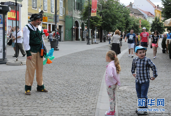小丑装扮的男子在步行街引逗小朋友。(新华网记者林惠芬摄)