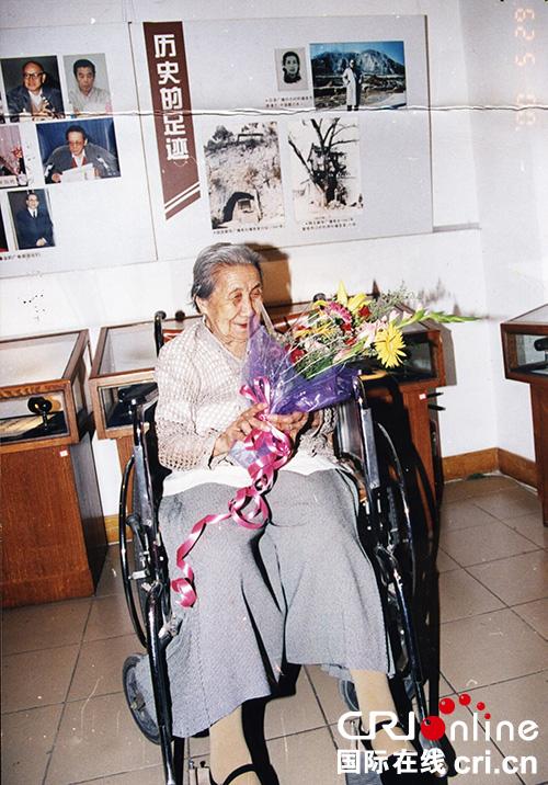 原清志老人在中国国际广播电台展厅的一角拍照留念,老人身后的展览即是当年她在延安新华广播电台对日广播的地方。