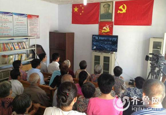 博兴县乔庄镇七合村村民齐聚村委会收看阅兵实况。