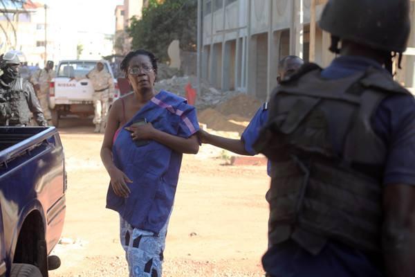 马里安全部队护送一名被解救的人质离开酒店。(图片来源:新华社/法新社)