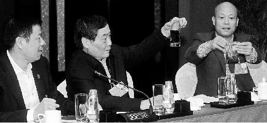 朱张金代表(右)将花生米泡出的黑水,传递给宗庆后(中)、戴天荣(左)等食品行业代表查看。