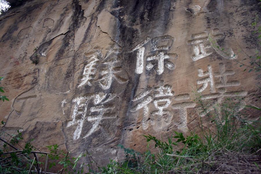 """2008年6月1日,利州区第三次全国文物普查工作队在大石镇境内开展文物普查时发现一处1933年红四方面军在此驻扎时书写的石刻标语。该石刻标语位于大石镇大石村二组(铁路隧道旁边山体的岩石上),距大石镇政府1.5公里左右。标语内容为""""武装保卫苏联""""六个石刻大字,落款为丁一(红三十一军九十三师部队番号代码)。(来源:利州灾后重建网)"""