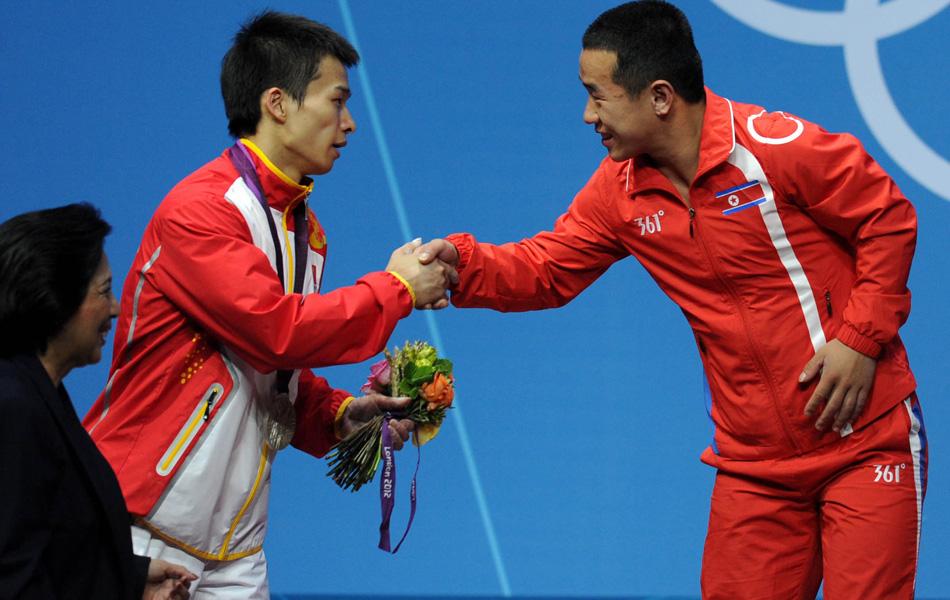 2012年7月30日,在伦敦奥运会举重男子56公斤级角逐中,朝鲜选手严润哲在B组出场却创造奇迹,他以293公斤的总成绩夺冠,并且创造了168公斤的挺举奥运会纪录。中国选手吴景彪以289公斤的总成绩获得银牌。图为吴景彪(左)与严润哲握手。