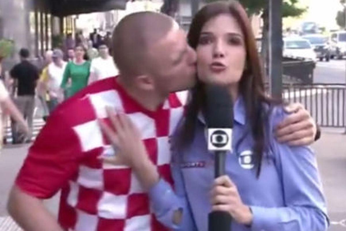 """据台湾""""东森新闻""""报道,克罗地亚在世界杯揭幕战中以1比3不敌东道主巴西,球迷们没能在球场上庆祝胜利。不过在赛场外,一名克罗地亚球迷至少可以庆祝他个人的胜利,因为他当街偷亲了正在播报新闻的巴西女记者,以这种方式为世界杯揭幕战惜败的克罗地亚国家队""""报仇""""。"""
