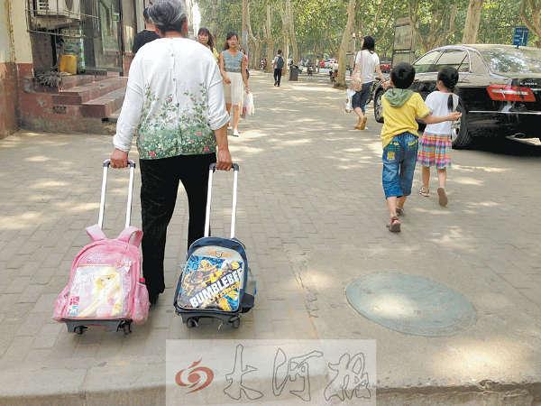 """夏日午后,郑州街头,通往学校的路上,一位头发花白的老人一人拉着俩书包,旁边跟着两个六七岁的孩子——这样的镜头在平时小学生上下学时间,稀松平常。前晚,本报摄影记者将所拍的照片上传微博后,立即引发网友热评。[现场] 一位老人拉着俩书包 前日(13日)下午2时30分许,烈日当头。郑州市大学路和康复前街交叉口附近,一位头发花白的老太太一手拉着一个书包,老人有些吃力,加上天气炎热,她的额头渗出了汗。她的前边,一个小男孩和一个小女孩在跑着玩着。""""是你不让他们背还是他们不背?&rd"""