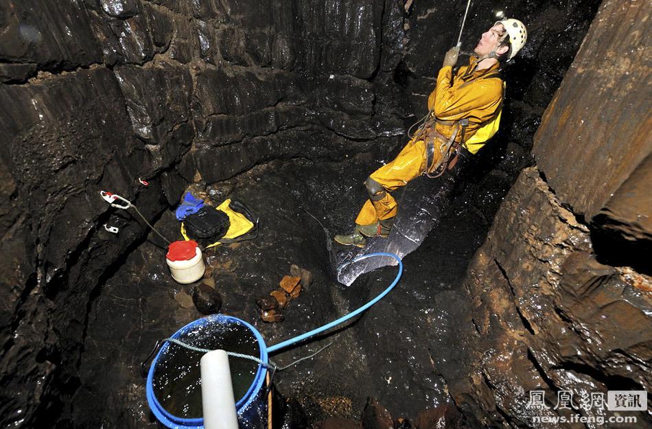 探险队员马克-理查德森正通过一根绳索向洞穴入口处攀爬.