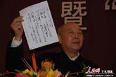 """原毛主席警卫队长在现场展示了毛主席亲笔书写的""""出差守则""""。(图片来源:人民网 文松辉 摄)"""