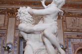 """《普鲁托和普洛塞尔皮娜》(Pluto and Proserpina)是年仅23岁的贝尔尼尼在1621-1622年创作。雕塑内容取自罗马神话故事。冥神普鲁托(Pluto)看上了谷物女神色列斯(Ceres)的女儿,他把她掠到冥界中,并改名为普洛塞尔皮娜。这尊两个人缠绕、扭打在一起的雕塑,从三个不同方向观察它会有三种不同的解释。从左边看普鲁托有力地抓住并托起普洛塞尔皮娜,而少女正在试图挣脱他的束缚;从前面看整个雕塑似乎是普鲁托正在炫耀他所获得的战利品,并把带她进入冥界;从右边看普洛塞尔皮娜脸上有她在向上天祈求时流下的眼泪,风吹起了她的头发,脚下那条守护地狱之门的三头犬(Cerberus)正在咆哮。贝尼尼惟妙惟肖地把掠夺的瞬间凝固在了这个雕塑上,从后面看普鲁托全身上下结实的肌肉和举起""""猎物""""时肌肉的变化都被刻画得淋漓尽致;雕像右边因为用力和兴奋普鲁托右手的四个手指深深地陷进了被掠走女人的大腿里,看上去有很强的质感和力感;而女主角微微张开的嘴唇仿佛是正在尖叫或寻求帮助。贝尼尼不仅从他们的眼神和神态上表现出了两人的极大差别,而且从肢体动作上似乎也能""""听到""""他和她要发出的呐喊和哀求。"""