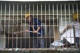 """5月29日,鹿丹村12栋3单元,透过一间房子的窗户可以看到远处深圳的标志性建筑京基100和地王大厦,前面破旧的老房子就是鹿丹村。此外,在鹿丹村小区里,随处可见墙体大片石灰、水泥脱落,钢筋裸露出来。参与建设小区的高级工程师刘先生说,这些都源于当初建设时候用了大量海沙。在那个年代,并没有明文规定禁止海沙大量用于建筑。 从最初发现房子质量问题的1996年左右,鹿丹村人就开始持续不断地投诉。1999年底,鹿丹村业委会成立。""""推动小区拆除重建是当时业委会成立后的两大任务之一。""""鹿丹村业委会主任陈克仁说。"""