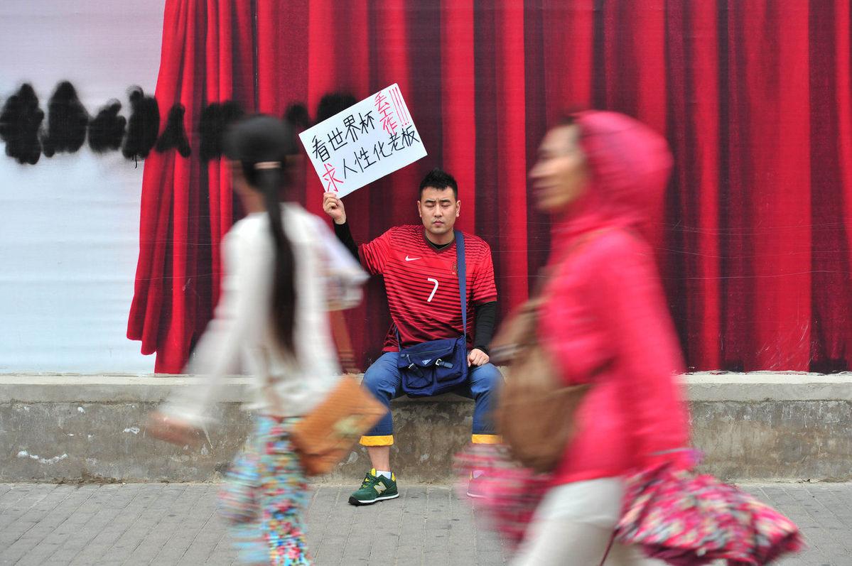 2014年6月25日,北京,在地铁崇文门d出口男子因看世界杯丢工作,身穿C罗球衣,坐在街头求职,求职牌子举过头顶。