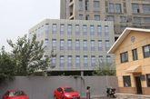 """2014年7月30日,江苏省南京市,市民从位于南京安德门地铁站附近的高层建筑""""瑞尔大厦""""前经过,这栋大楼主楼外立面已基本完工,未完工的裙楼则用画有窗子的塑料布遮挡,并且画有窗户,真真假假融合在一起。据公开资料显示,瑞尔大厦2004年开工,于2007年初停工,荒废至今。而南京青奥会将于2014年8月16日开幕,这栋荒废了10年的烂尾楼或是为青奥会糊塑料布""""遮羞""""。图为被塑料布遮住的停工大厦。"""