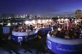 """说到影院,伦敦人绝对比谁都会玩,在大厦的楼顶,电影爱好者男女混浴躺在热水""""浴缸""""中,参与者不仅可以看到伦敦360度的全景,还能够通过楼顶树立起的大荧幕观看电影,同时又能享受沐浴,真是人生一大乐事啊!(实习编辑:温存)"""