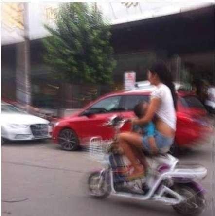 女子边骑摩托车边给孩子喂奶(图)