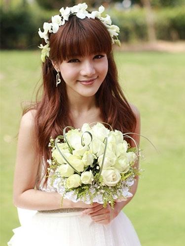 邓家佳一身洁白婚纱,头顶花状头纱,造型似仙女,脸上洋溢着幸福的微笑.图片