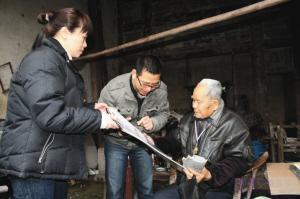 志愿者海少、阿茹为谢老戴上纪念章,讲述挂历中的照片。