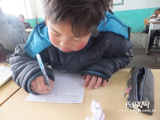 孩子在纸上写下心愿。石峥 摄