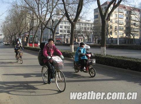 河北天气晴冷,骑车的人还是裹得严严实实的