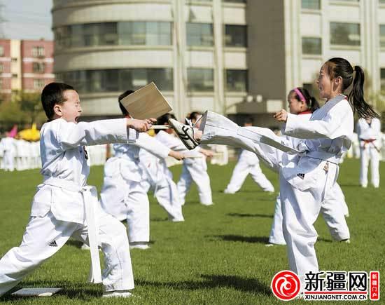 乌鲁木齐市39小学4年级的吴晓涵(右)和同学一起进行跆拳道表演.