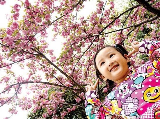 小女孩在樱花树下摆出可爱的造型拍照