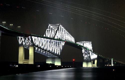 空中的光径为即将降落至羽田机场的飞机=25日晚,东京都江东区,长曝光
