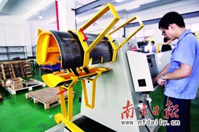 龙岗莱恩精机(深圳)有限公司的生产线上,工人正在组装工业机器人.