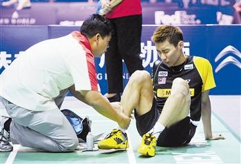 李宗伟(右)脚踝受伤。新华社发