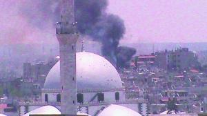 11日,叙利亚霍姆斯市Juret AL-Shayah街区遭轰炸,冒出浓烟。(截屏图)