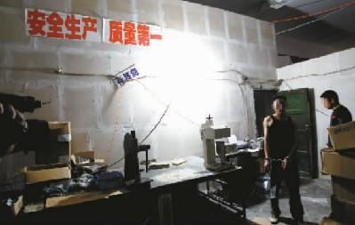 """■在制假窝点墙上贴着""""安全生产质量第一""""标语 记者 杨帆摄"""