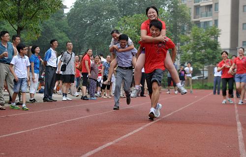"""邻居节趣味运动会上,居民们在进行""""背媳妇""""跑步比赛图片"""