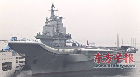 """26日中午12点半,""""辽宁舰""""上悬挂的满旗已被卸下,甲板上也只留下少数工作人员。早报记者 徐晓林 图"""