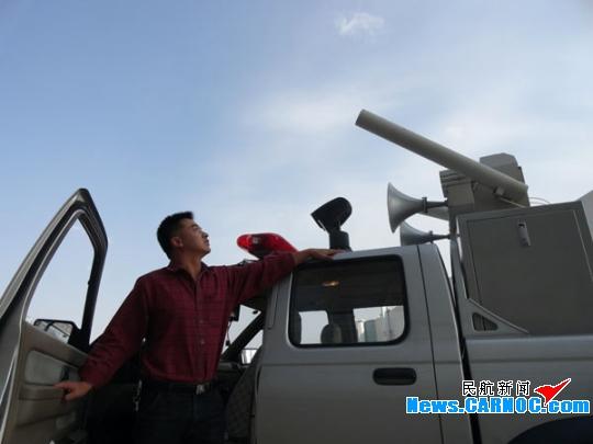 驱鸟工作人员眺望天空飞翔中的鸟