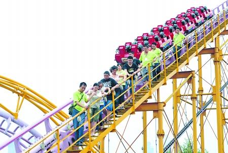 """昨日,重庆市游乐园,救援人员正将""""被困""""游客依次带下过山车轨道.图片"""