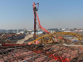 """一架黄色塔吊""""从天而降"""",""""横躺""""在工地上,从远处看,工地的部分钢结构"""