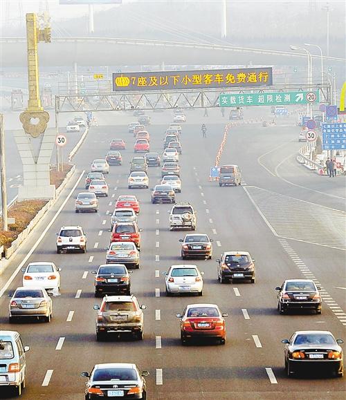 早晨,大批小型客车免费通过大连收费站驶入沈海高速公路. 新华社