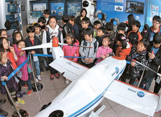 """""""活动项目的40余名小学生正在韩国航空宇宙研究院观看展示的飞机模型."""