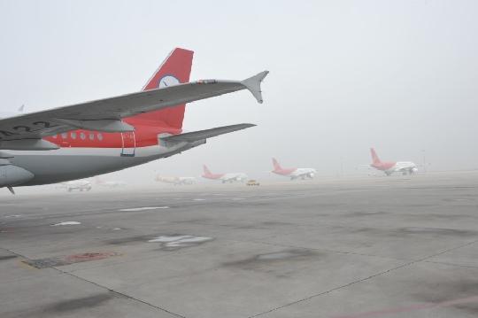 图1:机坪上能见度较低 民航资源网2013年3月26日消息:3月26日,西安咸阳国际机场(简称咸阳机场)遭遇2013年初春大雾天气,73个航班受影响。机场迅速启动大面积航班延误应急处置联动二级预案,各保障单位迅速行动保障航班。09:59,随着大雾消散,咸阳机场的航班逐步恢复正常。 大雾侵袭机场 73个航班延误 26日早晨咸阳机场被大雾笼罩,能见度不到100米,受此影响,从早上7点35分起的所有进出港航班全部延误。截止09:59,大雾共导致机场43个出港航班延误,30个进港航班延误。针对天气不正常的情况