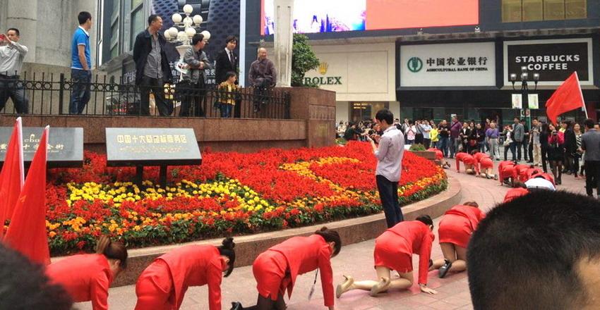2013年5月2日,当着数百围观者的面,一群人身着制服跪在繁华商业地段,一边爬圈圈一边喊加油。佚名/东方IC